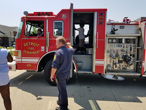 Detroit Fire Department fire truck with firefighter standing outside of it, holding the door. | What We Do at Communities of HOPE
