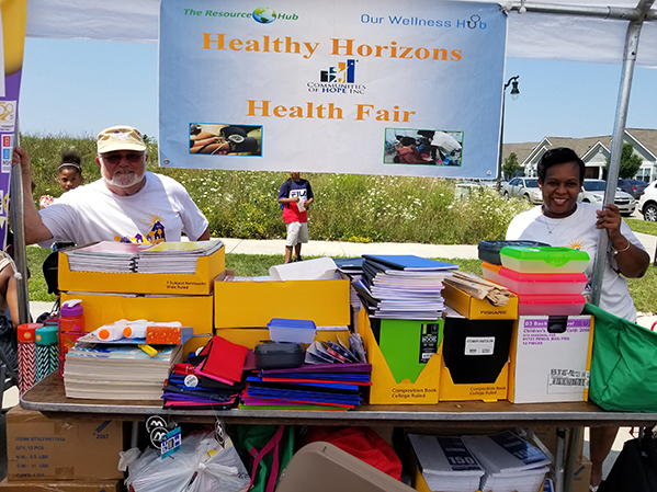 Two CoH volunteers standing at a table for Healthy Horizons Health Fair. | Educational Success | 4 Pillars of HOPE | Communities of HOPE