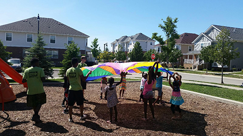 Kids playing outside with CoH volunteers helping. | What We Do at Communities of HOPE