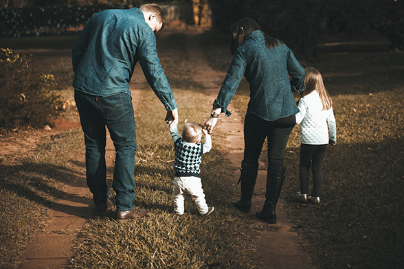 Family of four walking down a dirt road, holding hands. | CoH's 4 Pillars of HOPE