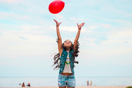 Girl jumping and reaching for a red balloon in the air. | CoH's 4 Pillars of HOPE