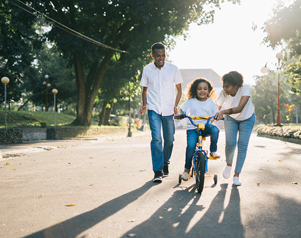 Parents helping their child ride their bike. | About CoH | Communities of HOPE