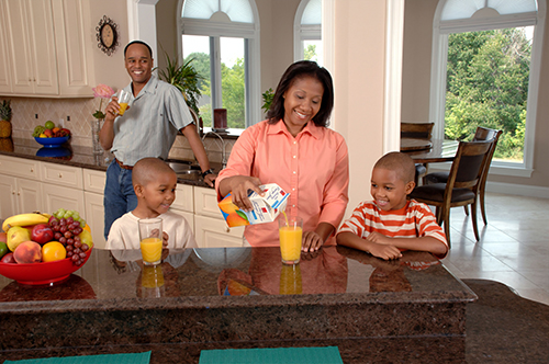 Family of 4 in the kitchen, drinking orange juice together | Healthy Living | 4 Pillars of HOPE | Communities of HOPE